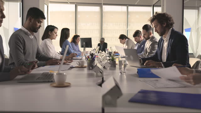 group of multi-tasking entrepreneurs working at conference table in the office. - large group of people stock videos & royalty-free footage