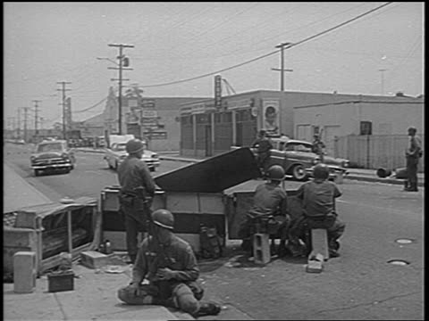 stockvideo's en b-roll-footage met view group of national guardsmen behind barricade / watts race riots low angle / newsreel - 1965
