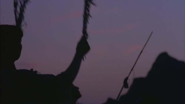 stockvideo's en b-roll-footage met a group of native americans perform a traditional dance at golden-hour. - ceremonie
