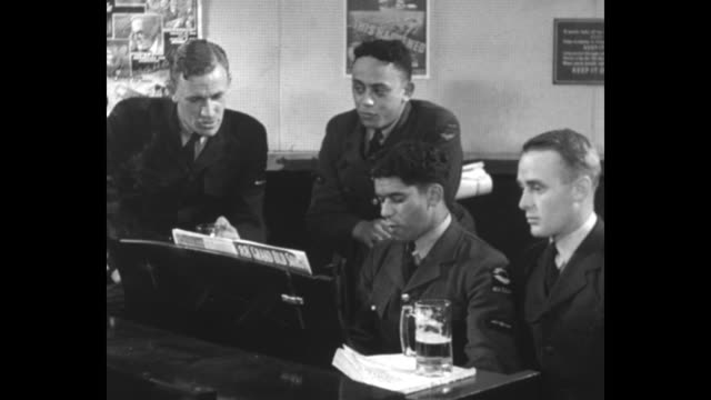 group of new zealand and australian air force men sit around piano in mess hall, sing a marching song; mugs of beer sit on piano as one of the men... - only girls stock videos & royalty-free footage