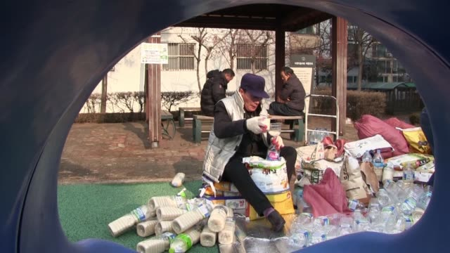 A group of North Korean defectors filling rice and propaganda in empty plastic bottles in the city of Seoul South Korea North Korean Defector Kim...