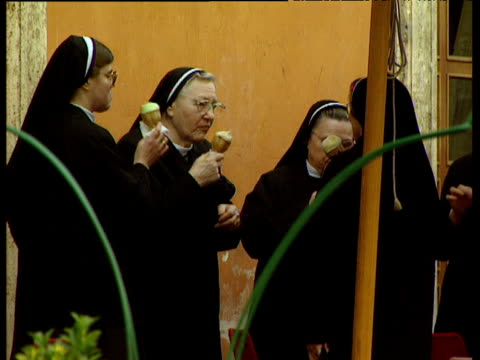 vidéos et rushes de group of nuns eating ice cream cones - contraste