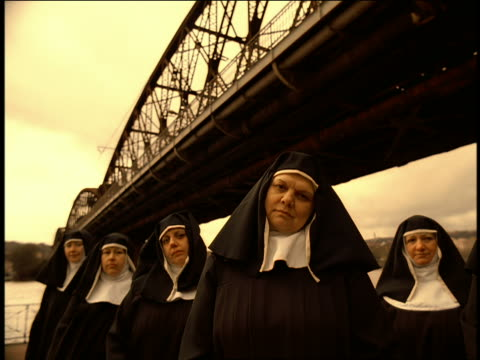 vídeos de stock, filmes e b-roll de ms group of nuns standing under bridge bobbing heads to beat of music / prague - nun