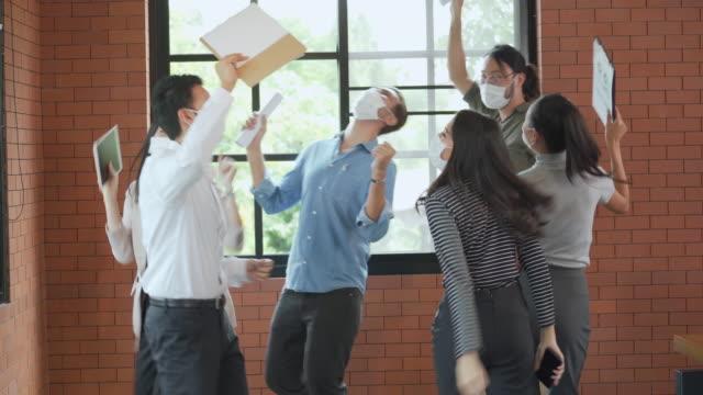 vidéos et rushes de groupe d'employés de bureau dansant et célébrant ensemble portant le masque de visage dans le bureau pour protéger covid-19 - féliciter