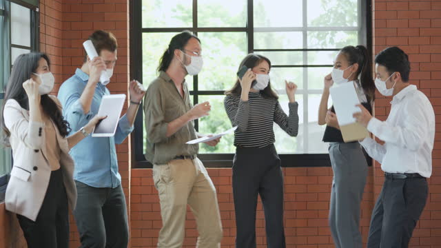 group of office workers dancing and celebrating together wearing face mask in office to protect covid-19 - place of work stock videos & royalty-free footage