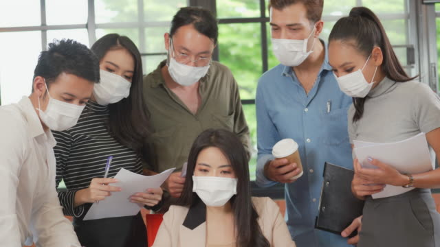 group of office workers meeting and wearing face mask in office to protect covid-19 - unity stock videos & royalty-free footage