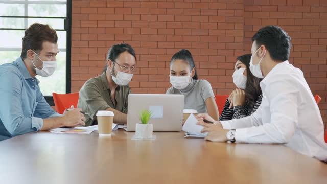 vidéos et rushes de groupe d'employés de bureau se rencontrant et portant le masque facial dans le bureau pour protéger covid-19 - réunion du personnel