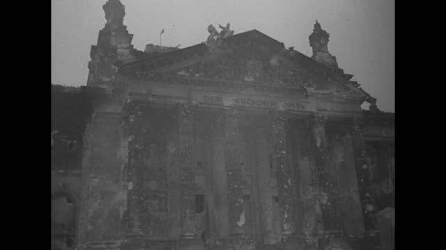 group of officers standing in front of heavily damaged reichstag building / group of officers standing in square damaged buildings in background /... - arrendersi video stock e b–roll