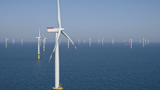 aerial group of offshore wind turbines producing energy in sunshine - propeller stock videos & royalty-free footage