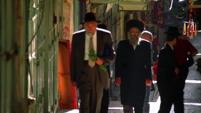 vídeos de stock, filmes e b-roll de ms group of orthodox jewish men walking towards camera in narrow street, israel, jerusalem - de braços dados