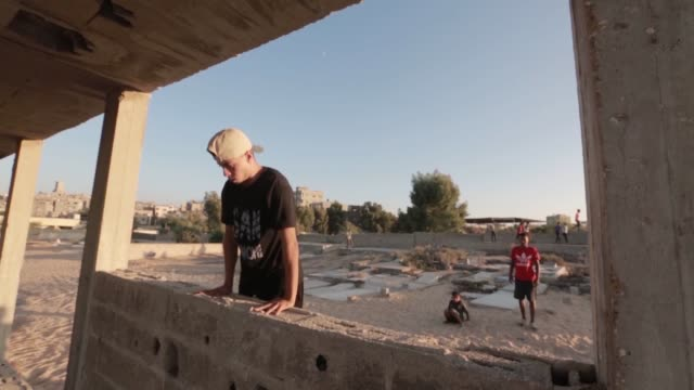 a group of palestinian teenagers has been practicing parkour in the blockaded gaza strip among the damaged buildings and rubble despite the... - israel palestine conflict stock videos & royalty-free footage