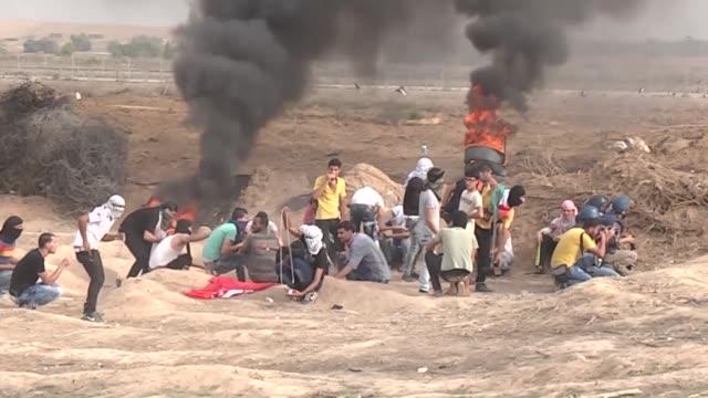 group of palestinians gather to protest israeli violations on al-aqsa mosque, on the east of gaza-israel border and israeli security intervene with... - イスラエルパレスチナ問題点の映像素材/bロール
