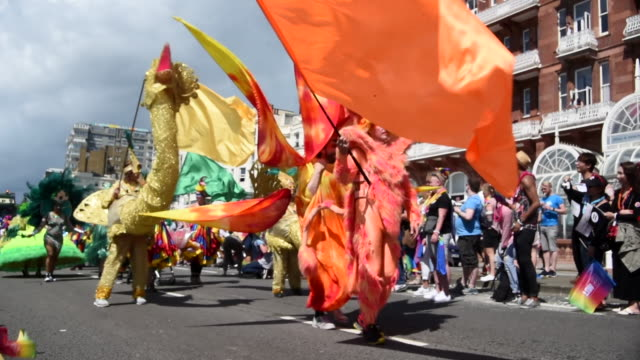 A group of paraders are dressed up in brightly coloured animal costumes and are waving brightly coloured flags as they walk down the street in the...