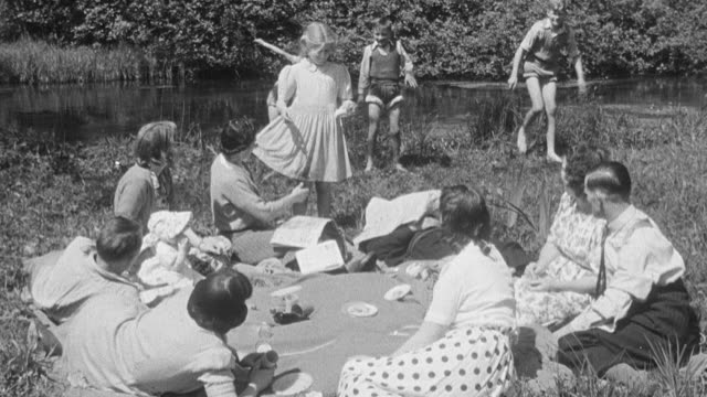 vídeos y material grabado en eventos de stock de 1950 montage group of parents sitting on a blanket having a picnic while children play and get dirty, ants nibbling on a picnicker, child pulling newspaper from napping dad, and child enjoying his lunch / united kingdom - blanco y negro