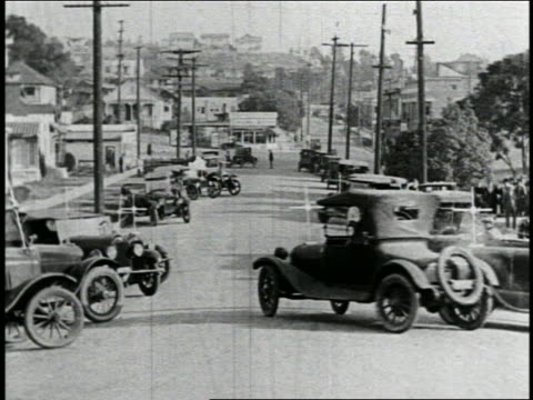 b/w 1925 group of parked cars driving with puffs of smoke into street + almost colliding / feature - スラップスティックコメディ点の映像素材/bロール