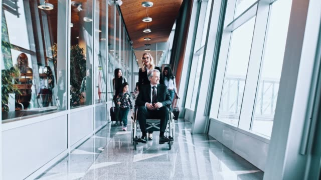 a group of passengers including a senior man on wheelchair passing the corridor in the airport - wheelchair stock videos & royalty-free footage