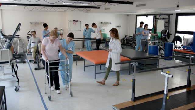 group of patients during physical rehab working with their therapist while female orthopedist checks on each patient holding a tablet - walking frame stock videos & royalty-free footage