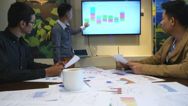 人々 のグループは、プレゼンテーションのグラフと会っています。 - 報告書点の映像素材/bロール