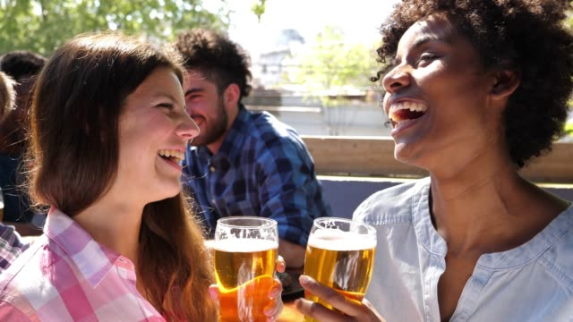 Group of people at a bar laughing and drinking beer very happy