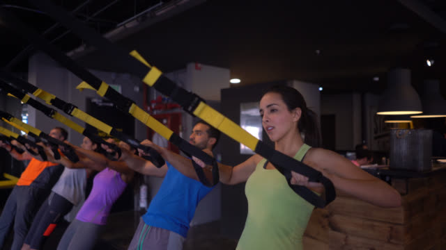 Group of people at a suspension strap class at the gym doing pull ups