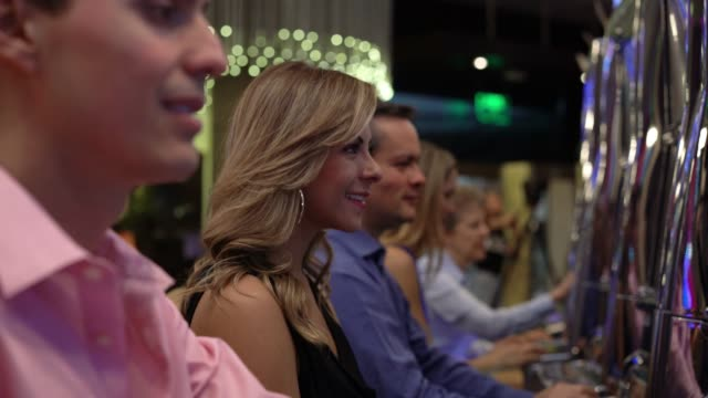 group of people at the casino playing on slot machines enjoying it - coin operated stock videos & royalty-free footage