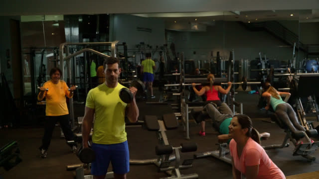 group of people at the gym working out on different machines very focused - exercise machine stock videos & royalty-free footage