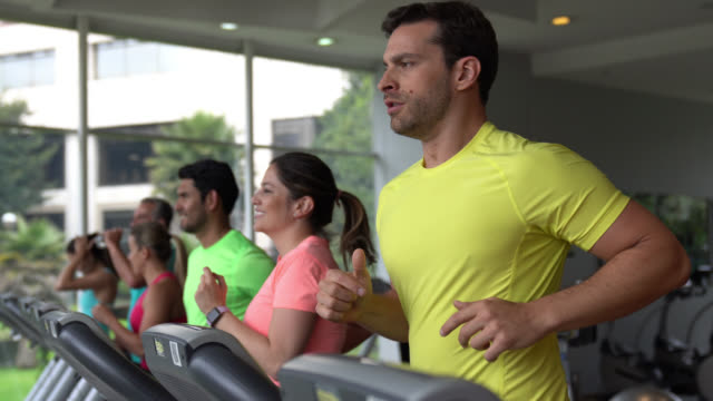 group of people at the gym working out on treadmills some looking cheerful others focused - treadmill stock videos & royalty-free footage