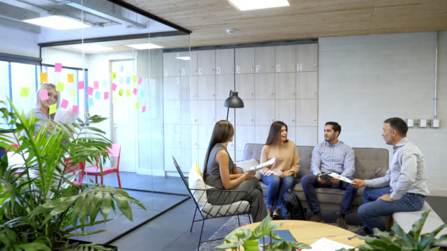 Group of people at the office discussing something while sitting on the couch and woman working behind with adhesive notes and a document all looking very happy
