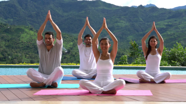 Group of people at yoga class outdoors sitting on yoga mats looking happy while doing exercises