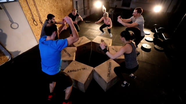 Group of people box jumping in the gym
