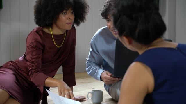 group of people brainstorming ideas on floor of office - weibliche angestellte stock-videos und b-roll-filmmaterial