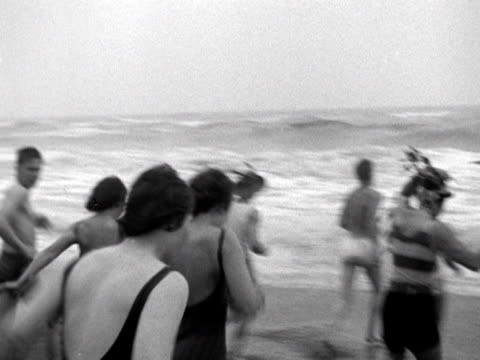 vídeos de stock e filmes b-roll de group of people brave the sea at the traditional christmas day swim at folkestone. 1960. - enfeites para a cabeça