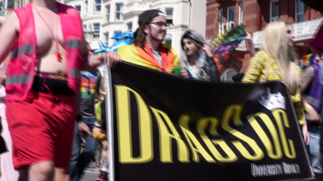 A group of people carry a banner supporting drag in the Brighton Gay Pride Parade 2017