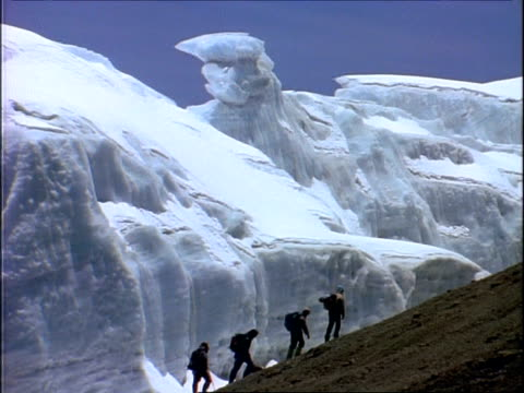 WA Group of people climbing up mount Kilimanjaro, against massive ice formations in background, Tanzania, Africa