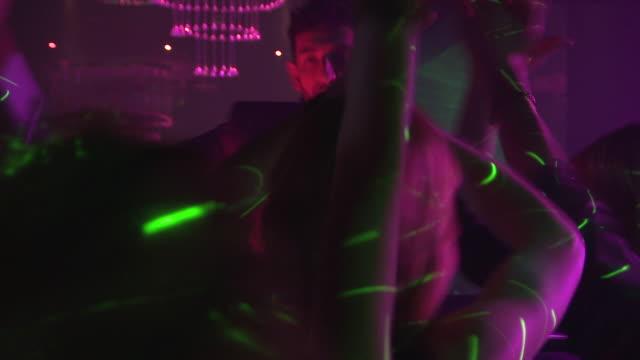 stockvideo's en b-roll-footage met ms pan group of people dancing in night club, dj in background / london, uk - club dj