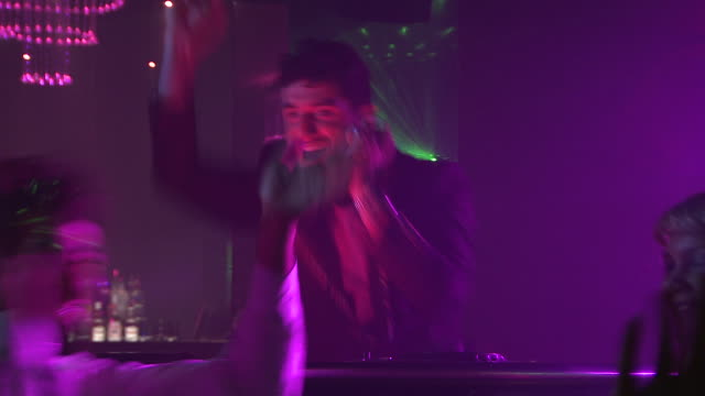 vidéos et rushes de ms group of people dancing in night club, dj in background / london, uk - dj