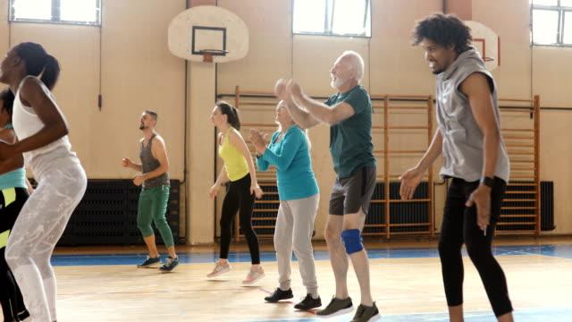vídeos de stock, filmes e b-roll de grupo de pessoas que dançam na classe latin do aerobics - aula de exercícios