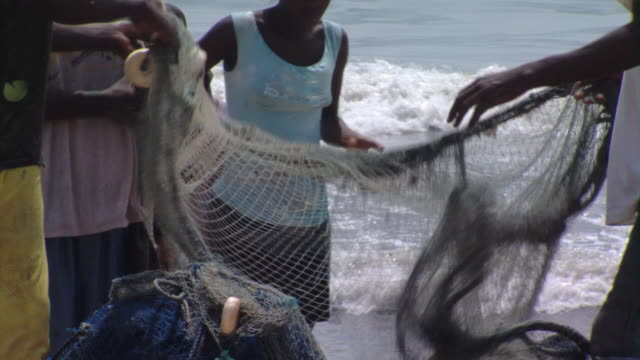 cu group of people detangling fishing net on beach, tamale, ghana - ghana stock videos & royalty-free footage