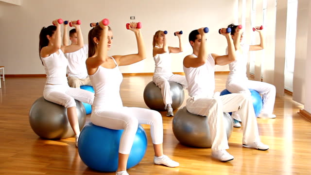 group of people doing exercise on fitness balls with dumbbells. - fitness ball stock videos & royalty-free footage
