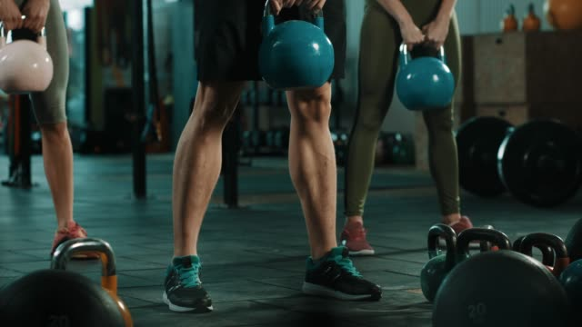 Group of people doing exercise with kettlebell in gym