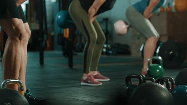 group of people doing exercise with kettlebell in gym - kettlebell stock videos & royalty-free footage