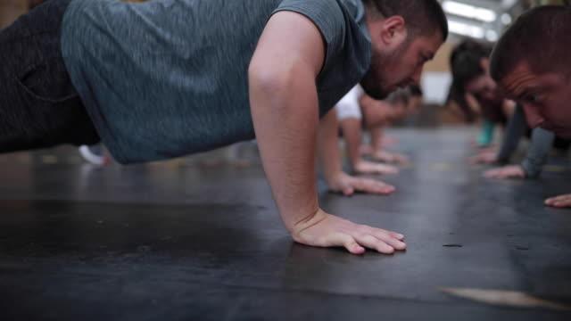 vídeos y material grabado en eventos de stock de grupo de personas haciendo flexiones de brazos en cruz formación - entrenamiento sin material