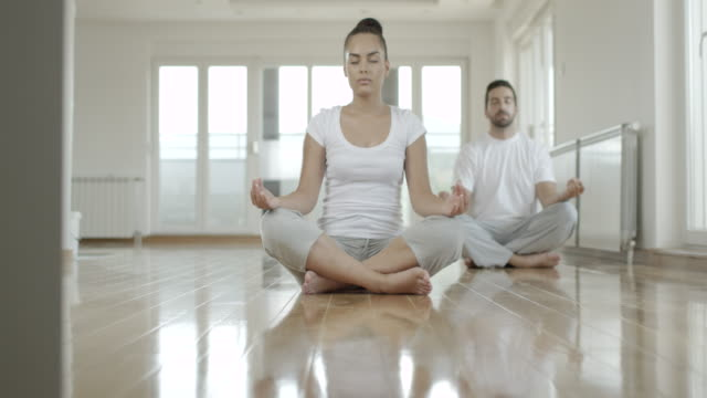 vídeos de stock e filmes b-roll de grupo de pessoas fazendo exercícios de ioga - ginásio