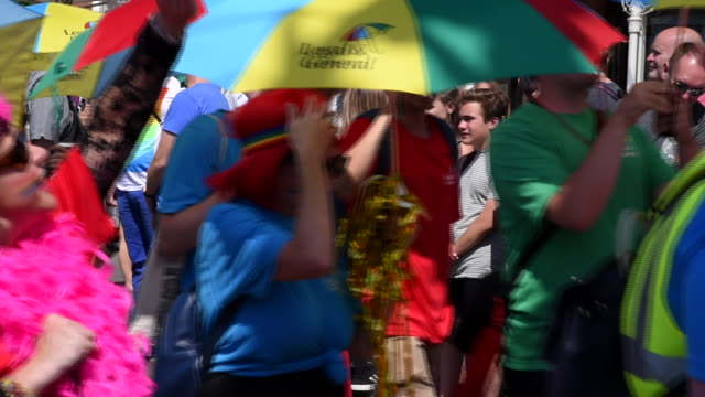A group of people dressed up in bright colours carry and parade with equally brightly coloured umbrellas in the Brighton Gay Pride Parade 2017