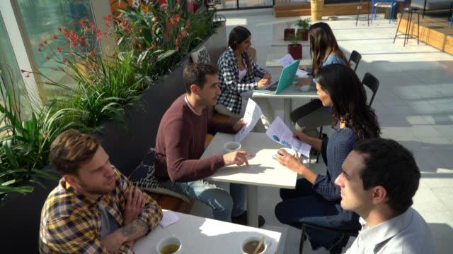 オフィスの屋外テラスでのコーヒーブレイク中の人々のグループ - casual clothing点の映像素材/bロール