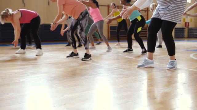 vídeos de stock, filmes e b-roll de grupo de pessoas que apreciam uma classe de zumba - aula de exercícios