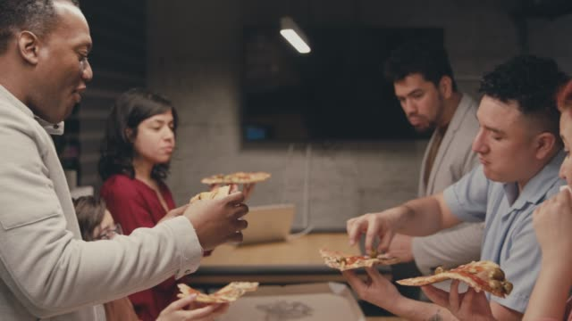 group of people enjoying pizza together at the office - lunch stock videos & royalty-free footage
