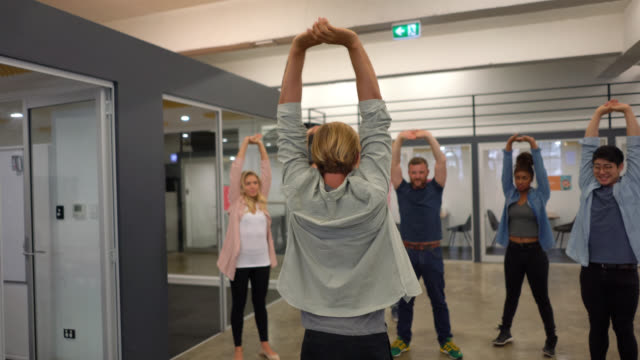 group of people exercising at the office following someone on stretching exercises - stretching stock videos & royalty-free footage
