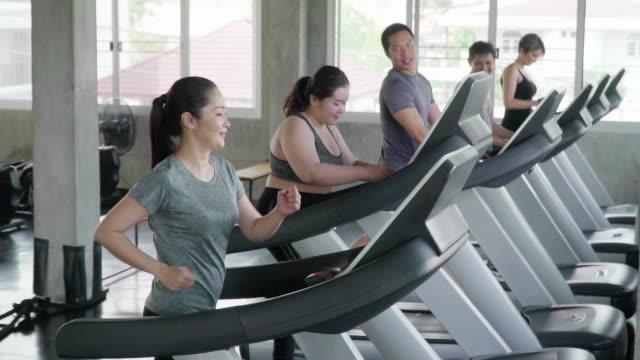 トレッドミルで運動する人々のグループ - 大柄点の映像素材/bロール