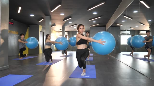 group of people exercising with fitness ball in gym - pallone per fitness video stock e b–roll